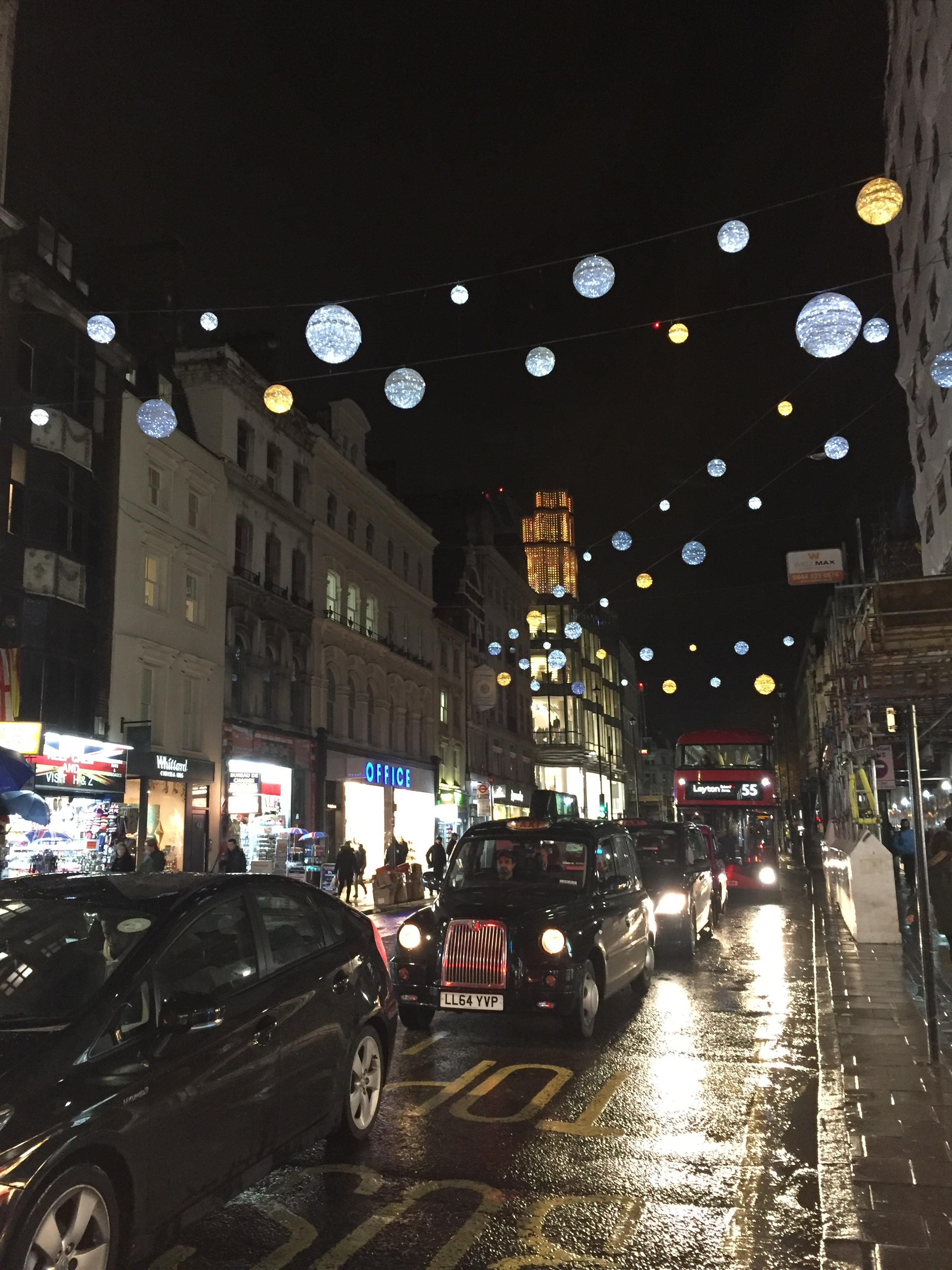 Oxford street, decorated for the holidays. Also notice the iconic London cab and double decker bus.