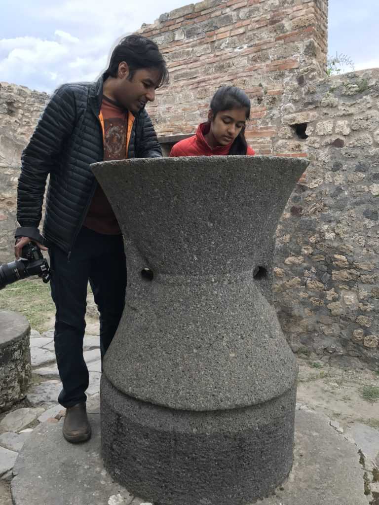 A typical grain grinder. The two holes in the middle in the middle section held long wooden poles. A person would pour grains from the top while grinder was rotated using the wooden poles. Flour would fall out from between the two rocks into a circular container which would be placed where Nirmal is standing.