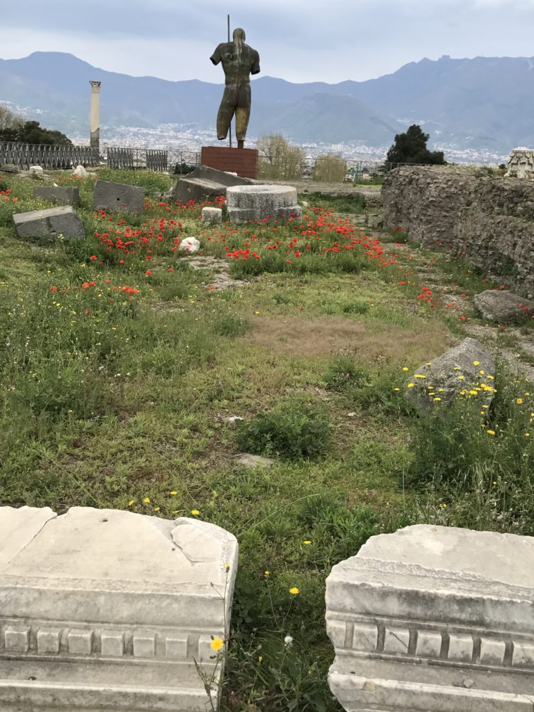 Amongst the ruins and red poppies stands the decapitated sculpture by Mitoraj, of a man looking down to the valley.