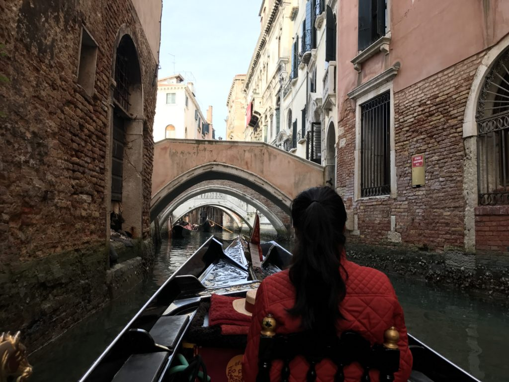 Going under many bridges on a gondola in Venice.