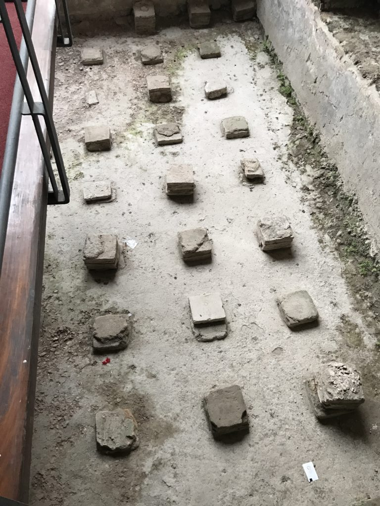 Bricks added gaps between the foundation and the floor. The floor was then heated by hot air circulating beneath. This would be so much more comfortable than the hot air circulating in our houses.