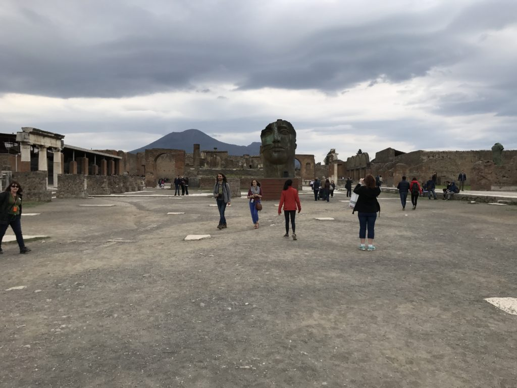 The Forum of Pompeii is quire remarkable, even in today's ruins. Looking straight ahead is the majestic Mount Vesuvius. In front of the mountain is the temple of Jupiter(partially hidden behind the statue of a face). To the right is the wool and cloth market and to the left is the public speaking section. On both sides of the temple of Jupiter are entrances to the main markets. Behind is the main entrance and city hall.