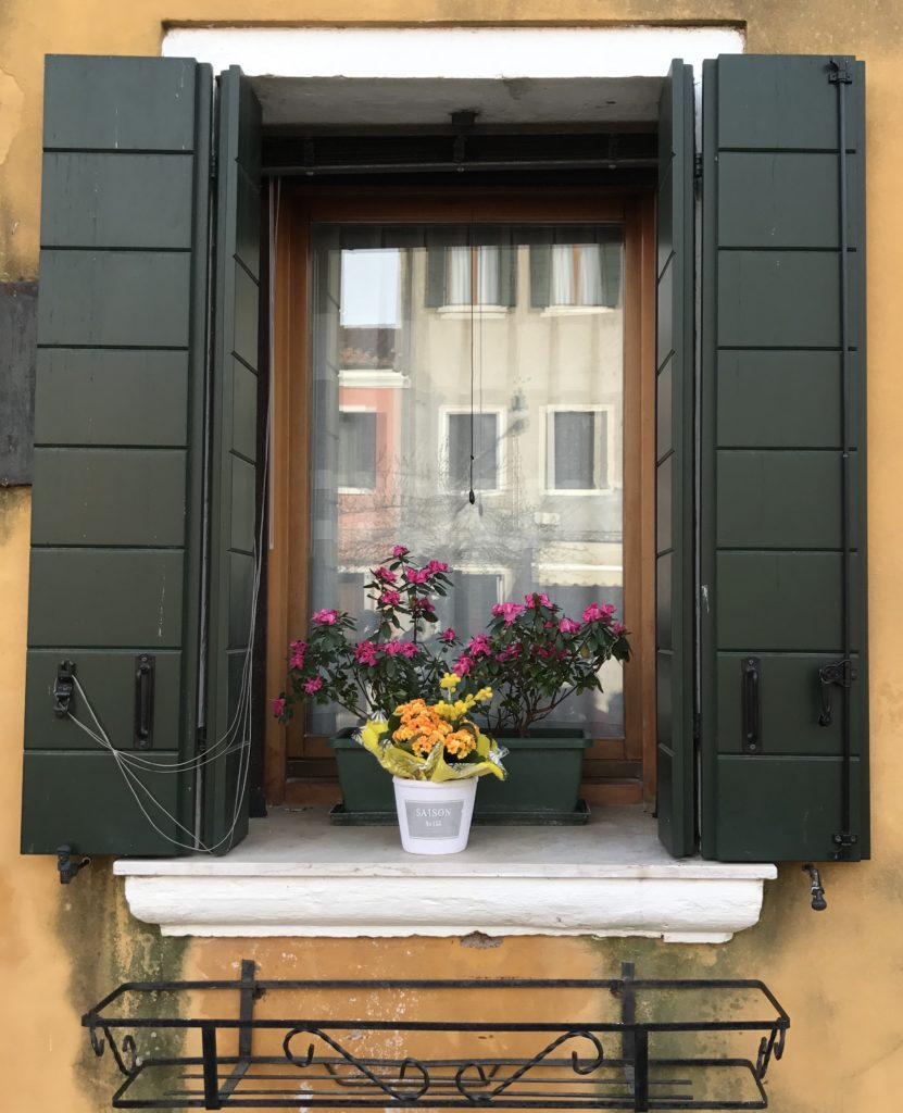 Houses in Venice and surrounding islands have these interesting shutters that look beautiful when open and help the room go dark when shut. Very functional, sturdy and artistic window covering.