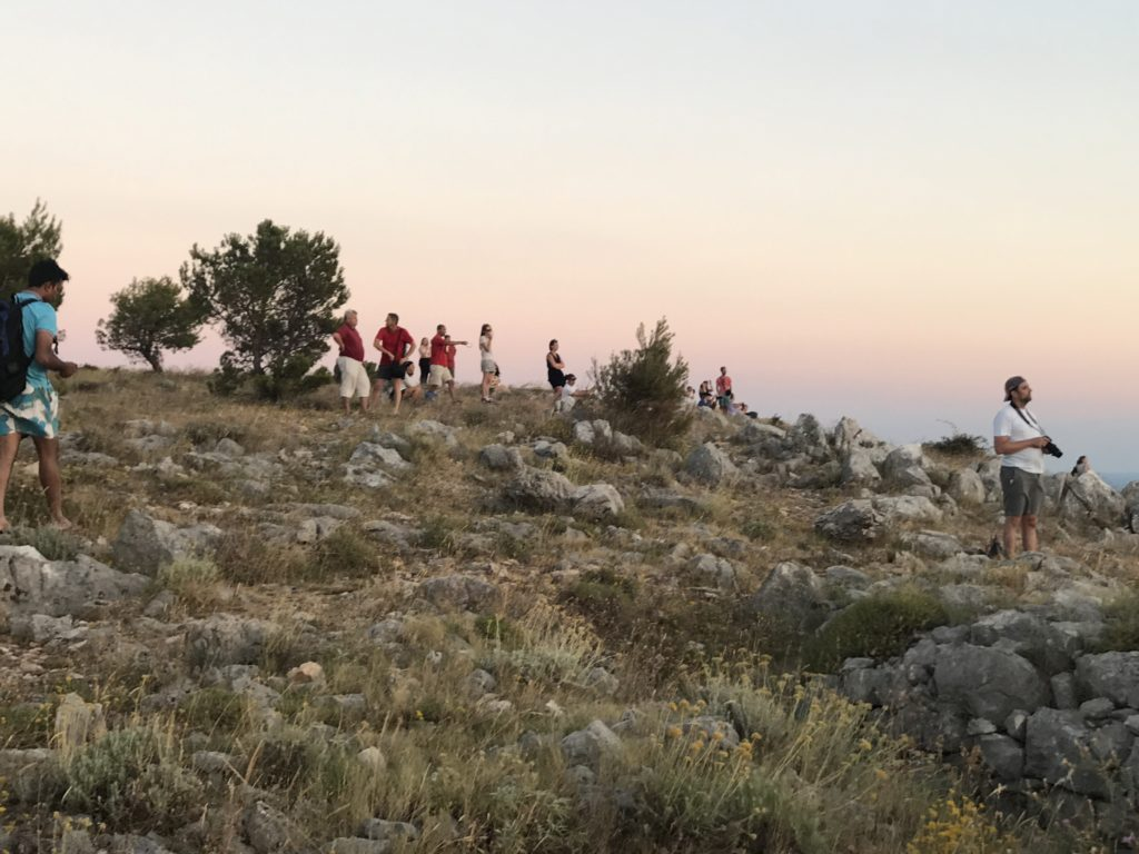 People camp on the hillside to enjoy the view of the sun setting in the Adriatic.