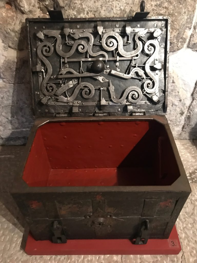 A portable iron chest showing the complicated locking mechanism under the lid. While it was common in Europe in those centuries, very few remain. Each of the chests on display is unique in its design and locking mechanism.