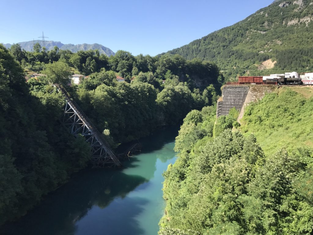 The remains of bridge in Jablanica, still lie fallen in the river. Also, on the right is an old train that may have used the bridge. I love the color of the hills and river! How stunning!