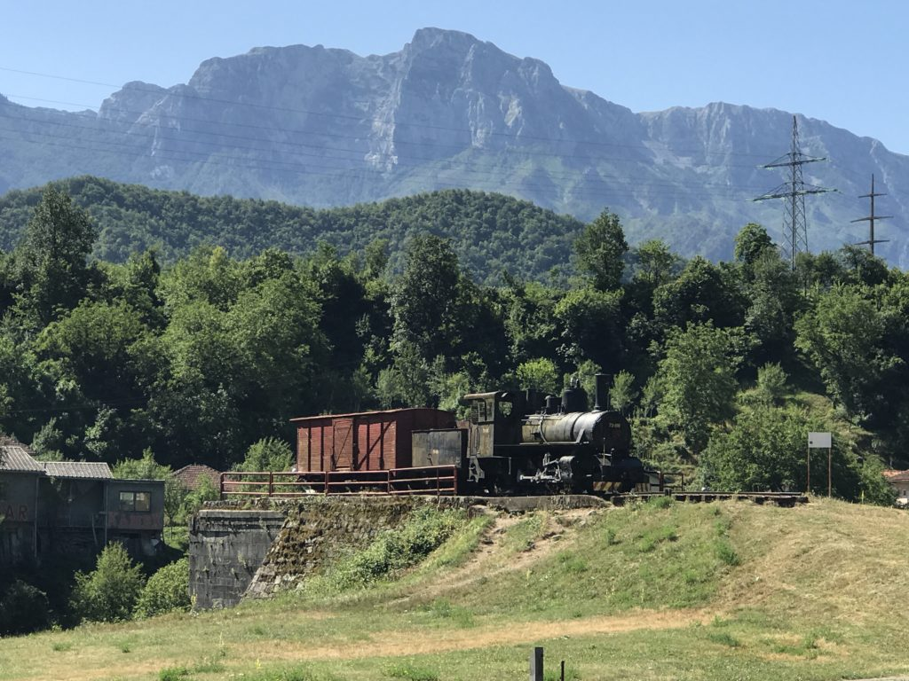 Majestic mountains tower over the old train.