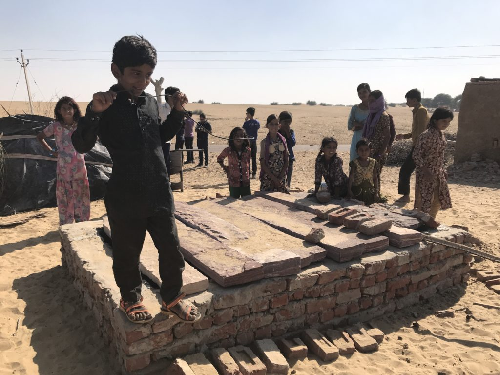 The village kids show us the underground water tank. Presumably covered to prevent evaporation and contamination.