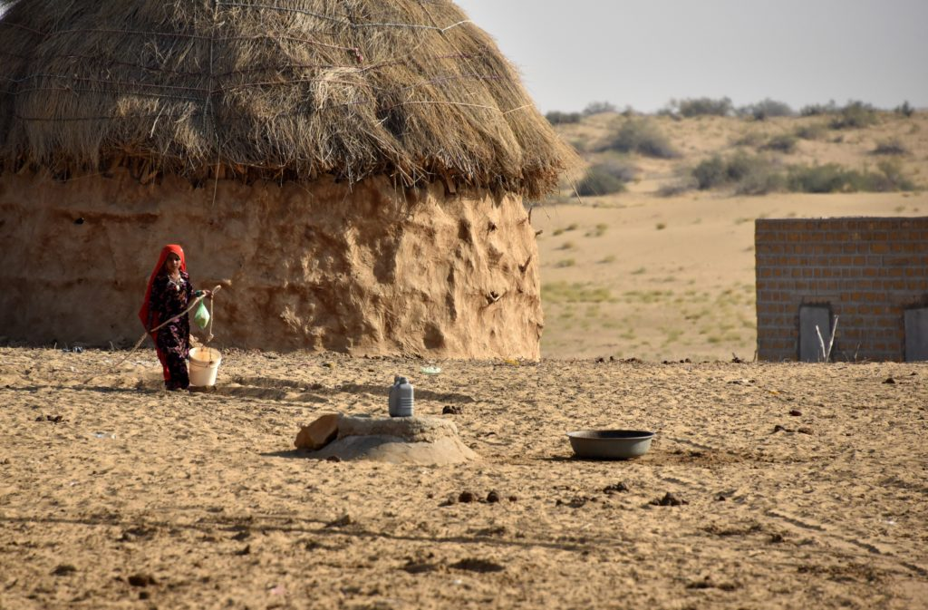 A girl fetching water from a kund (well) near her large hut shaped house.