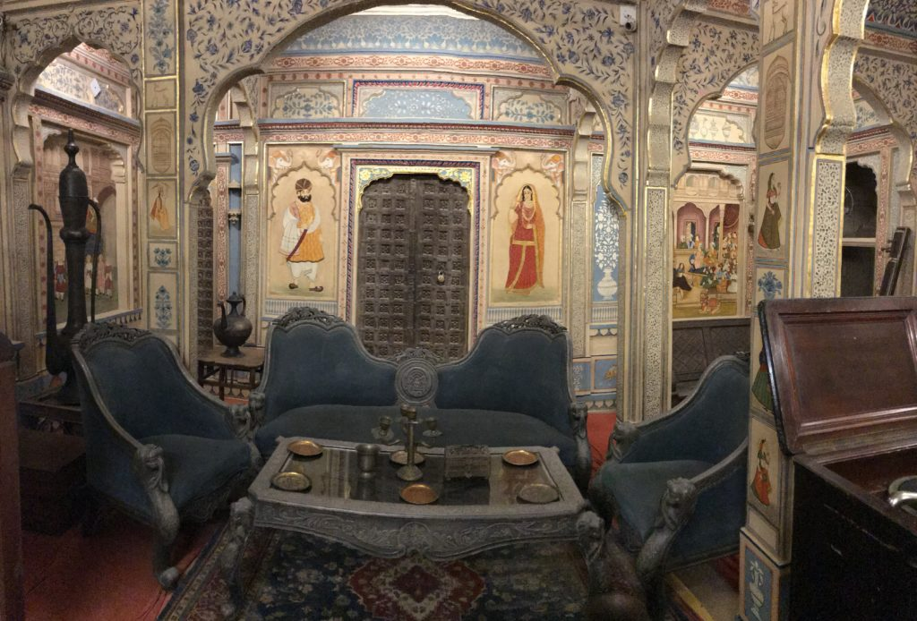 The formal sitting room has many sources of entertainment, such as a record player, sitar, hukka etc.