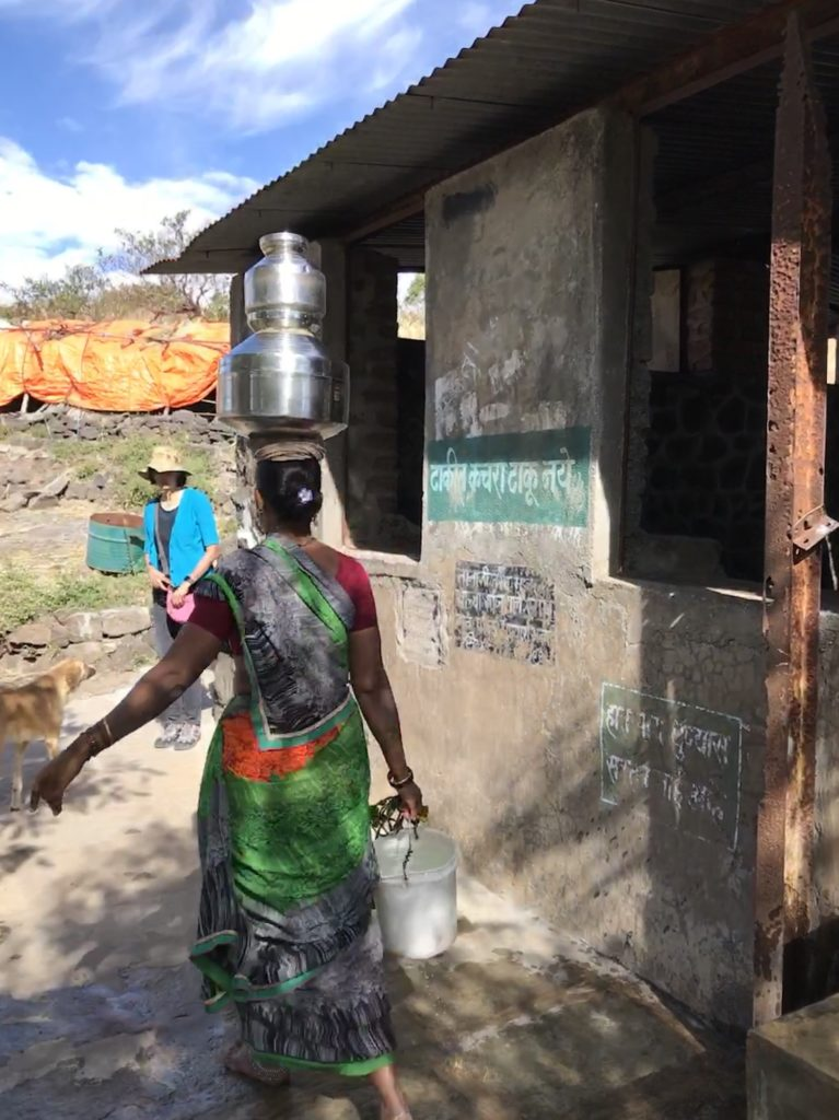 A woman takes water for her family.