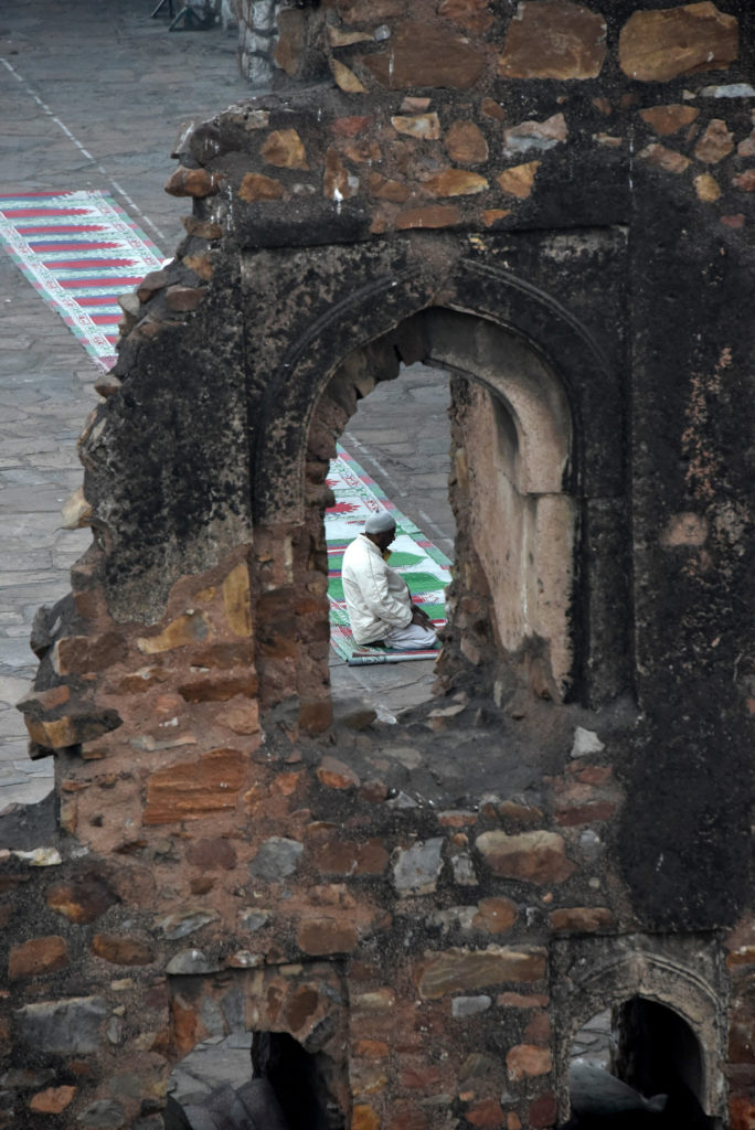 A practitioner praying in the open courtyard of Jami Maszid in Feroz Shah Kotla, Delhi