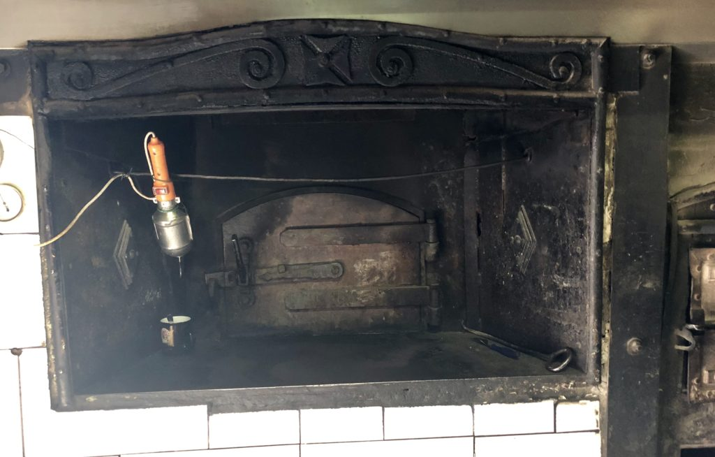 The hundred year old oven still used every day to make the famous treats in ... The wood is inserted into the small trap door to the right. The flames heat the large 16 pizza over from the back. The staff uses the main door to handle the food. Its unbearably hot in the summer and cozy warm in the winter