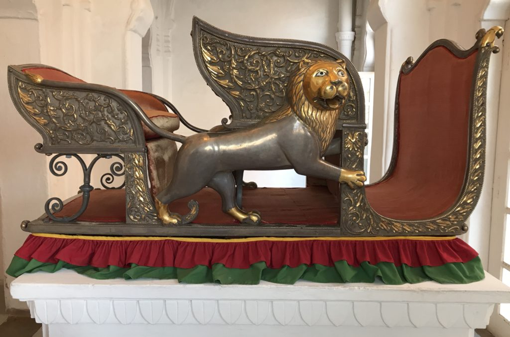 The elephant howdah (the King's seat on an elephant) is made on a wooden frame and embossed with silver. It has iron rings to strap onto the elephant. It's from the 19th century.