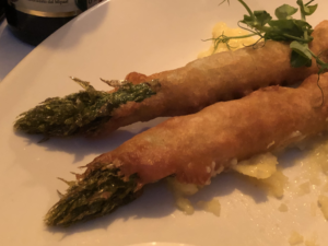 Asparagus rolled in blankets with pea shoots and some sauces.