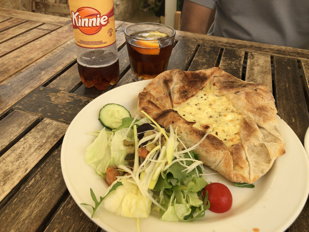 A ftira, Malta's answer to the Italian pizza. It's a homemade pastry lined with potatoes and sheep cheese. Served with salad and marinated vegetables. Kinney is a local drink from Gozo.