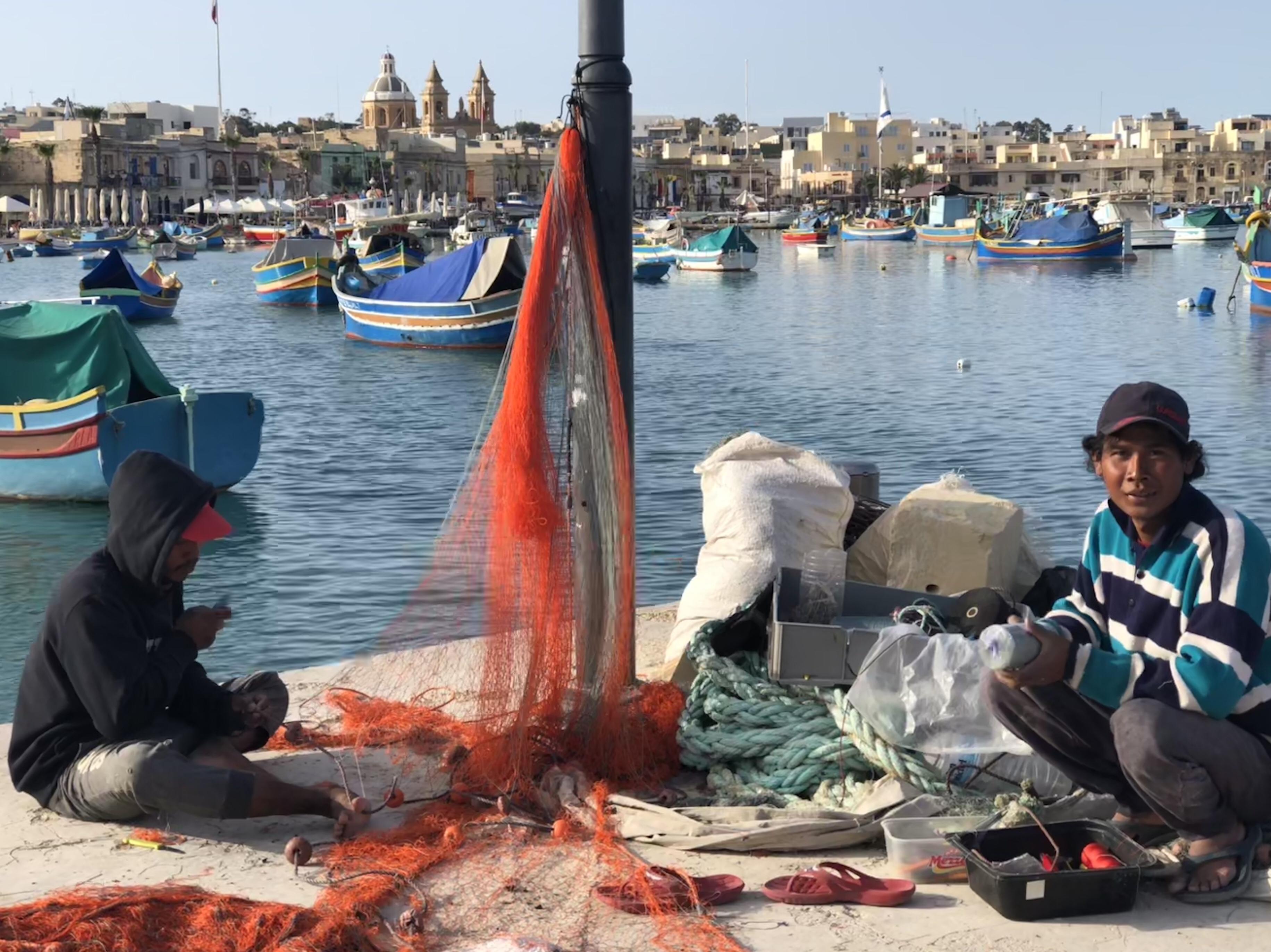 Migrant workers repairing nets in Marsaxlokk