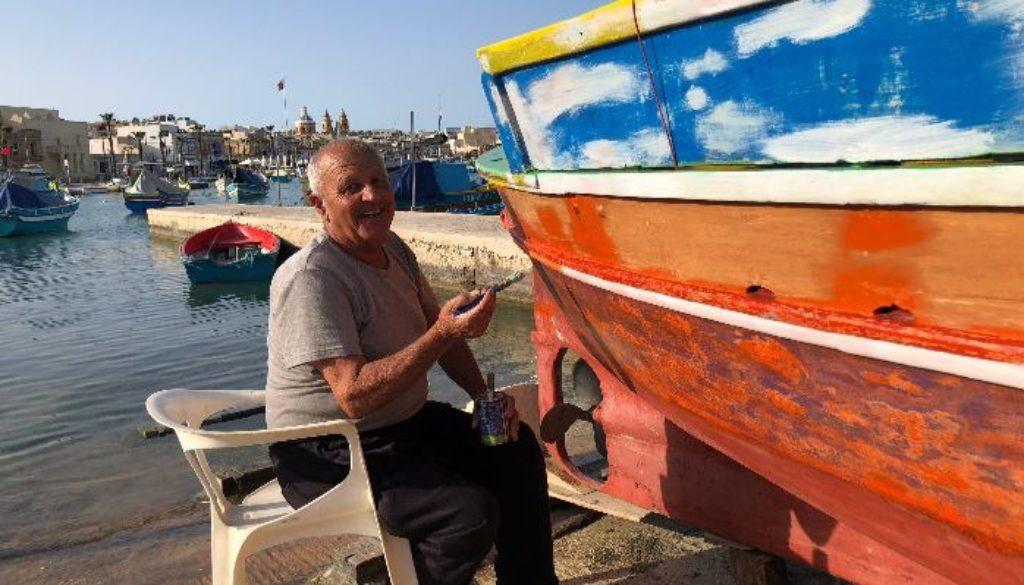 A fisherman in Marsaxlokk painting his boat.
