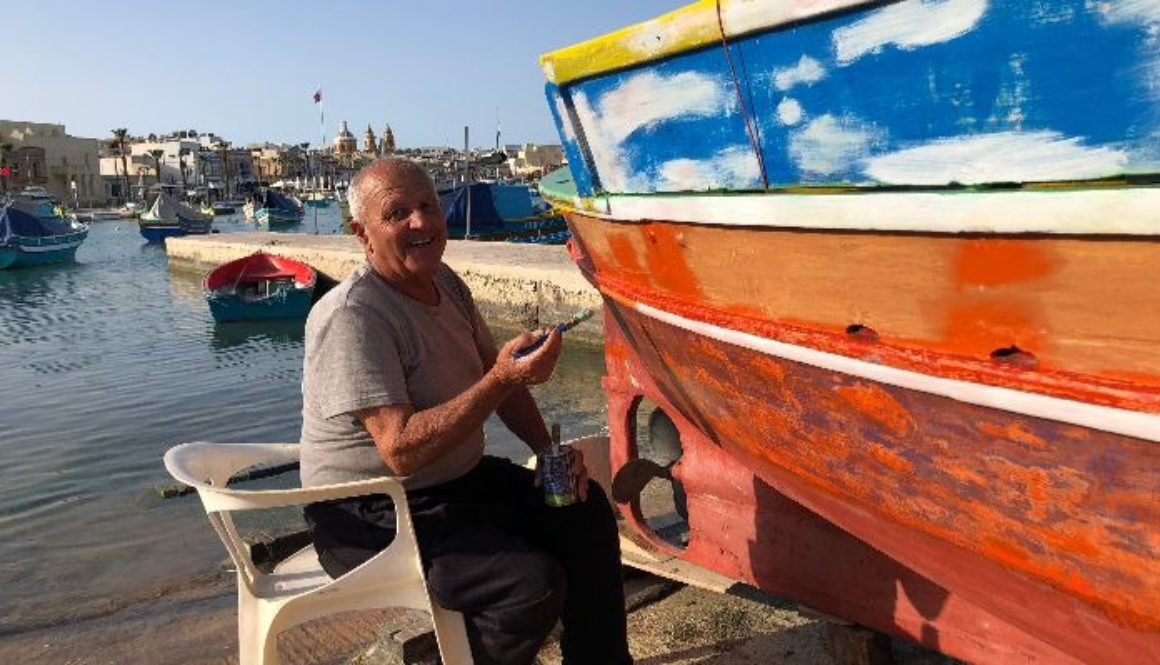 A fisherman in Marsaxlokk painting his boat.