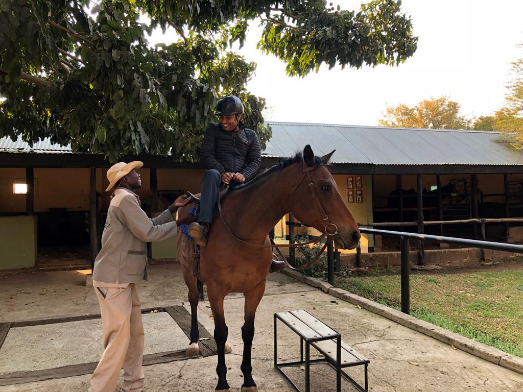 Likwit got Nirmal well settled on King's Glory for our horseback ride in Livingston, Zambia