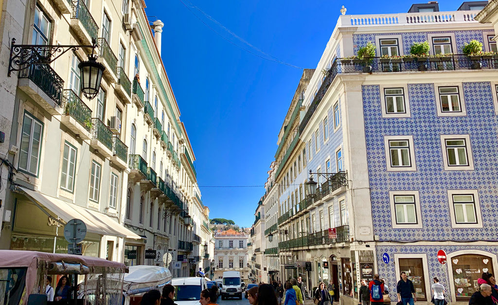 A quintessential Lisbon street with Portuguese tiled buildings and matching balconies.